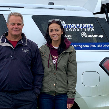 Man and woman standing in front of company truck.