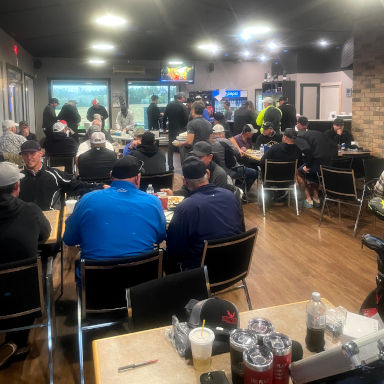 Men seated and standing in a golf club dining room.